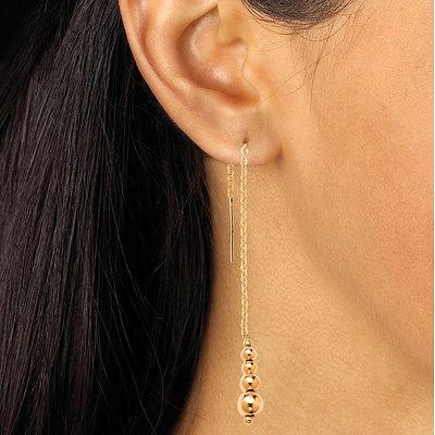Золотые серьги-протяжки с бусинами на модели